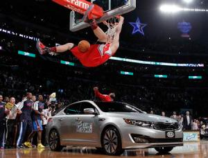 Los Angeles Clippers' Blake Griffin hangs on the rim after jumping over a car in Los Angeles.